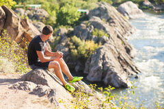 Il turista si siede su una roccia ed esamina un fiume della montagna Immagini Stock