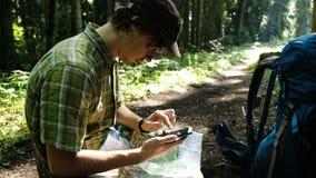 Il turista stanco con uno zaino si siede nella foresta ed usa una mappa elettronica sul suo telefono, controlla l'itinerario su u video d archivio