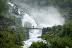 Il turista sul ponte e sulla cascata spruzza Fotografie Stock Libere da Diritti