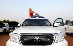 Il turista è sul tetto dell'automobile fuori strada durante il viaggio del deserto del Dubai Fotografia Stock Libera da Diritti