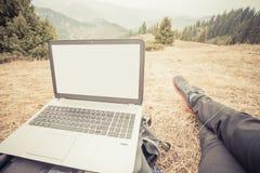 Il turista utilizza a distanza il computer portatile e si rilassa alla montagna Fotografia Stock