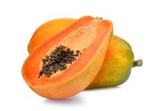 Il tutto e la metà della papaia matura fruttificano con i semi su bianco immagini stock
