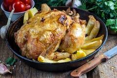 Il tutto ha arrostito il pollo con la patata su una pentola Immagine Stock