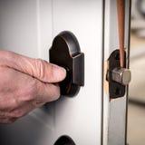 Il tuttofare applica una goccia di olio lubrificante sul chiavistello senza molla di scatto di una porta del garage fotografia stock libera da diritti