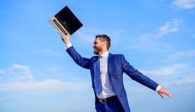 Il a un rêve L'homme inspiré tient l'ordinateur portable au-dessus de se L'entrepreneur inspiré par homme d'affaires sent aller p photo libre de droits