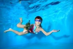Il Underwater nella bambina della piscina nuota con un giocattolo a disposizione, esaminando la macchina fotografica e sorridere immagine stock libera da diritti