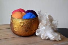 Il vagabondaggio variopinto della lana delle pecore in un rame ha colorato la ciotola di vetro Fotografia Stock