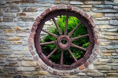 Il vagone di legno antico e stagionato del carretto spinge dentro i vecchi Bu di pietra dell'azienda agricola Fotografie Stock Libere da Diritti