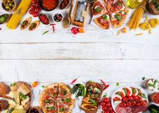 Il vario genere di alimento italiano è servito su legno immagini stock