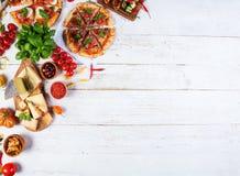 Il vario genere di alimento italiano è servito su legno fotografie stock