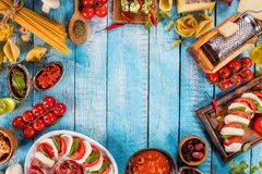 Il vario genere di alimento italiano è servito su legno immagini stock libere da diritti
