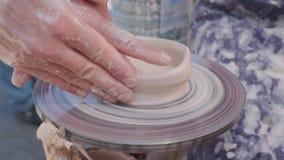 Il vasaio crea il prodotto su una ruota del ` s del vasaio sulle terraglie di filatura del tornio del ` s del vasaio Artista Oper stock footage