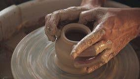 Il vasaio crea il prodotto su una ruota del ` s del vasaio Terraglie di filatura stock footage