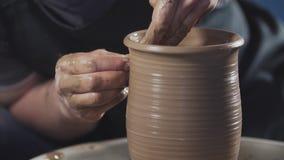 Il vasaio crea il prodotto sulle terraglie di filatura del tornio del vasaio al rallentatore stock footage