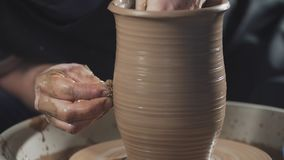 Il vasaio crea il prodotto sulle terraglie di filatura del tornio del vasaio al rallentatore video d archivio