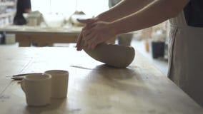 Il vasaio dei giovani sta impastando la massa dell'argilla sulla tavola nell'officina delle terraglie video d archivio