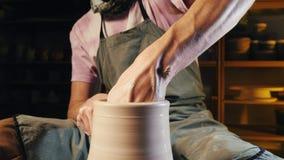 Il vasaio esperto modella il prodotto dell'argilla - brocca - con gli strumenti delle terraglie Chiuda su delle mani maschii che  stock footage