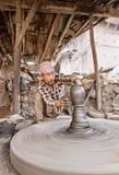 Il vasaio indigeno di Bhaktapur fa le terraglie con la ruota di tornitura fotografia stock