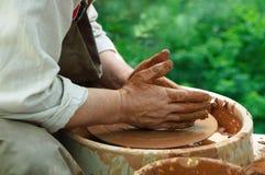 Il vasaio lavora ad un tornio da vasaio fotografie stock libere da diritti