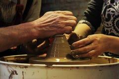 il vasaio matrice con esperienza insegna all'arte di fabbricazione dell'argilla di vasi 'sulla ruota di s Immagine Stock Libera da Diritti