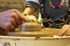 il vasaio matrice con esperienza insegna all'arte di fabbricazione dell'argilla di vasi 'sulla ruota di s Fotografia Stock