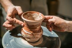 Il vasaio matrice insegna al bambino a come fare una brocca da argilla Immagine Stock