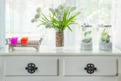 Il vaso con il fiore e l'annata decorano sulla tavola con il davanzale i Fotografia Stock Libera da Diritti