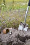Il vaso delle monete di oro si è raccolto con aiuto del metal detector, fondo dell'erba verde Fotografia Stock