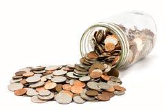 Il vaso delle monete si è rovesciato su una priorità bassa bianca immagine stock libera da diritti