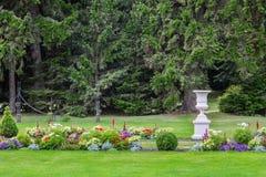Il vaso ed i fiori antichi bianchi in una località di soggiorno parcheggiano Fotografia Stock