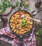 Il vaso saporito della pasta dei tortellini con le verdure sauce e cucchiai sul fondo rustico del tavolo da cucina con i piatti e Fotografia Stock