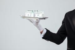 Il vassoio con soldi holded dalla mano del cameriere in guanto fotografie stock libere da diritti