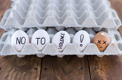 Il vassoio dell'uovo del cartone con le uova del pollo Concetto sociale violenza Fotografia Stock Libera da Diritti