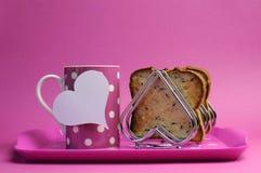 Il vassoio rosa della prima colazione con la tazza della tazza di tè del caffè del pois ed il cuore modellano lo scaffale del pane Fotografia Stock