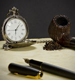 Il vecchi orologio, tubo, tabacco e penna. Fotografia Stock