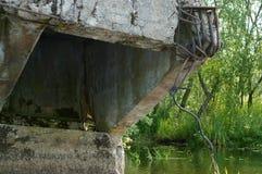 Il vecchio appoggio concreto del ponte, sopportante il ponte rotto nell'acqua Immagine Stock