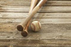 Il vecchio baseball ed i pipistrelli su legno ruvido sorgono Fotografie Stock Libere da Diritti