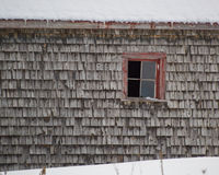 Il vecchio cedro stagionato scuote il granaio delle assicelle con l'inverno rosso della finestra Immagini Stock Libere da Diritti