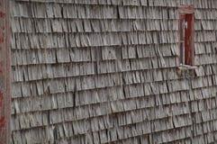 Il vecchio cedro stagionato scuote il granaio delle assicelle con la finestra rossa Fotografia Stock Libera da Diritti