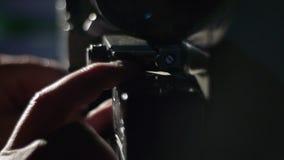 Il vecchio cineproiettore gioca in una stanza scura Un proiezionista, primo piano di una mano che carica un film in un cineproiet video d archivio