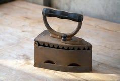 Il vecchio ferro su una tabella nei fasci Fotografia Stock Libera da Diritti