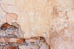 Il vecchio giallo misero stagionato incrinato dipinto ha intonacato il fondo sbucciato del muro di mattoni immagini stock libere da diritti