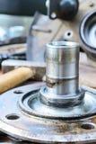 Il vecchio, hub di ruota lubrificato si trova su una tavola di legno Immagine Stock
