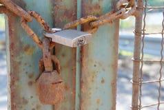 Il vecchio lerciume arrugginito del metallo fissa il recinto incatenato con la nuova serratura immagine stock