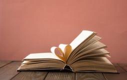 Il vecchio libro aperto della libro con copertina rigida, pagina decora in una forma del cuore per amore nel ` s del biglietto di fotografia stock