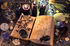 Il vecchio libro della strega con il pentagramma, le candele nere, i cristalli ed il rituale obietta fotografia stock libera da diritti