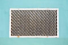 Il vecchio metallo ha modellato la griglia di ventilazione sulla parete intonacata Immagine Stock