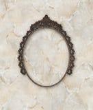 Il vecchio metallo ovale della cornice ha lavorato a fondo di marmo Immagini Stock Libere da Diritti