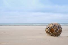 Il vecchio pallone da calcio di cuoio di calcio si siede sulla spiaggia di sabbia Immagini Stock