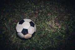 Il vecchio pallone da calcio o il calcio mette sull'erba verde per la scossa Esaminando macchina fotografica Immagine Stock